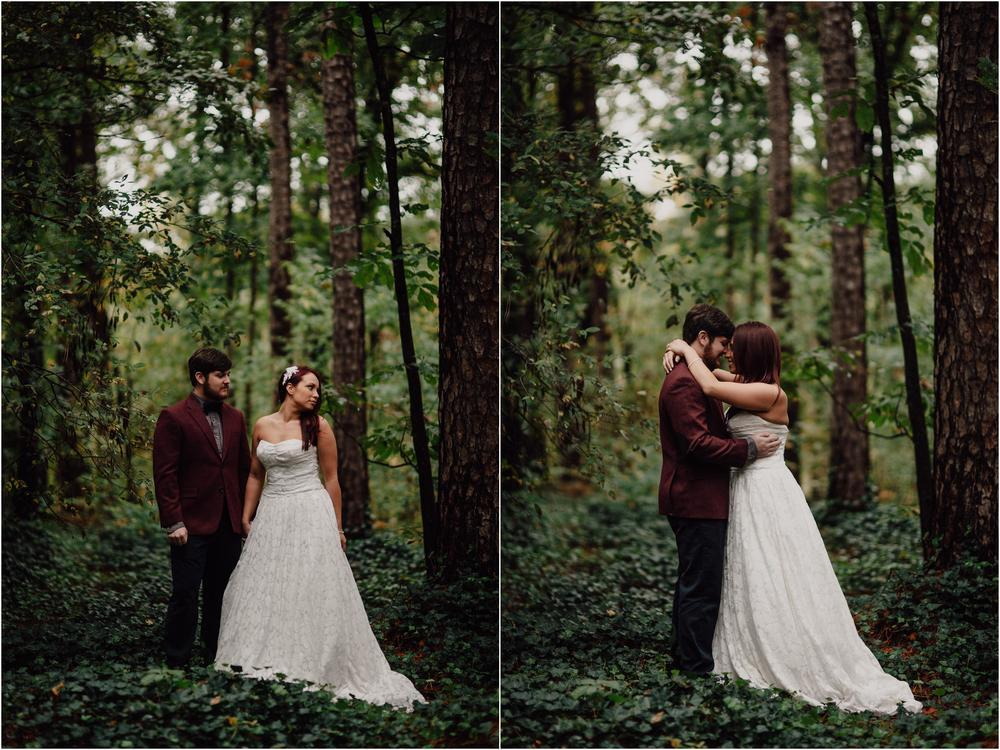 groom with maroon suit and bride in white dress in middle of the forest