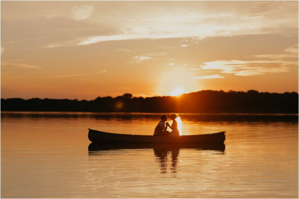 couple rowing across lake at sunset
