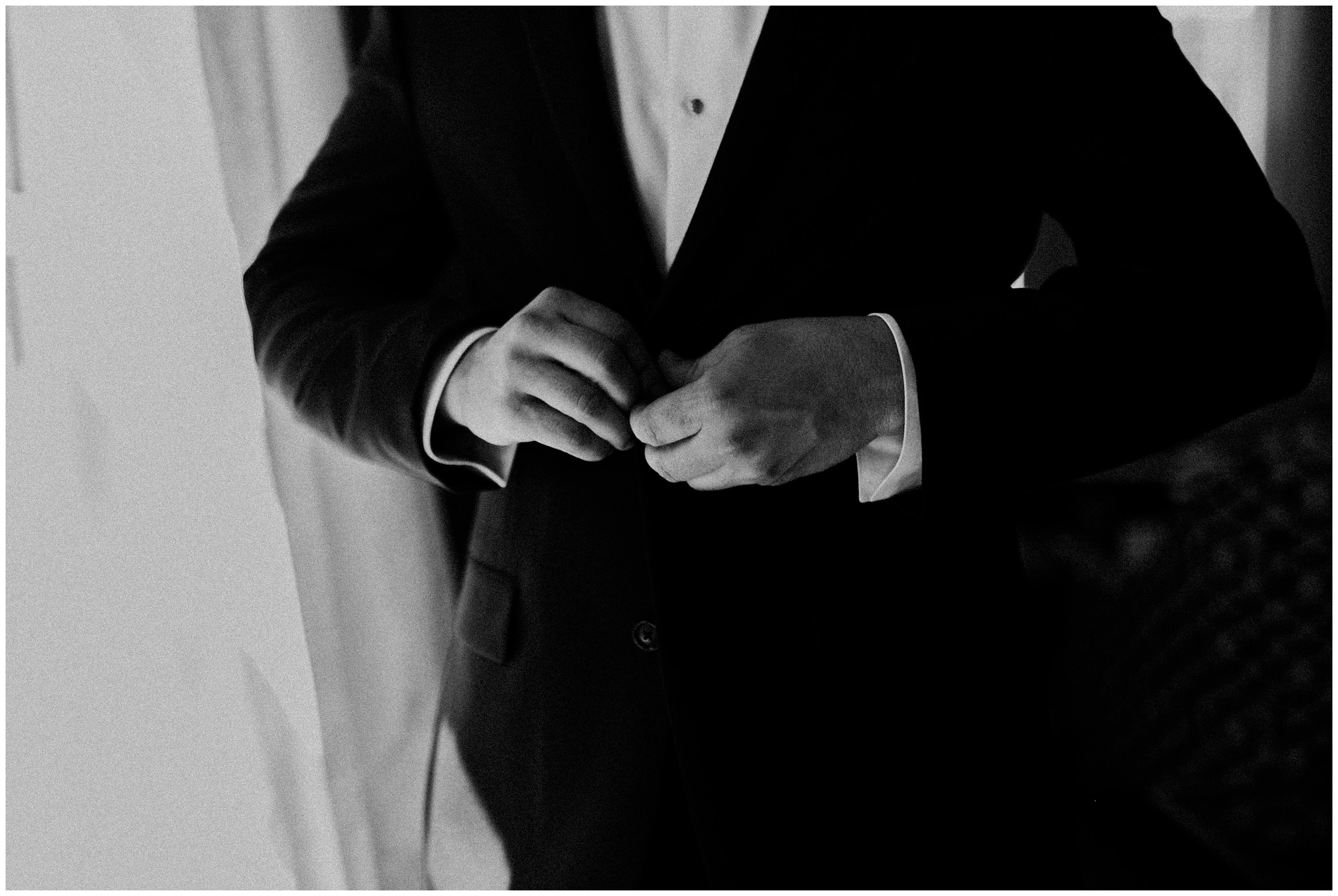 groom buttoning up his suit