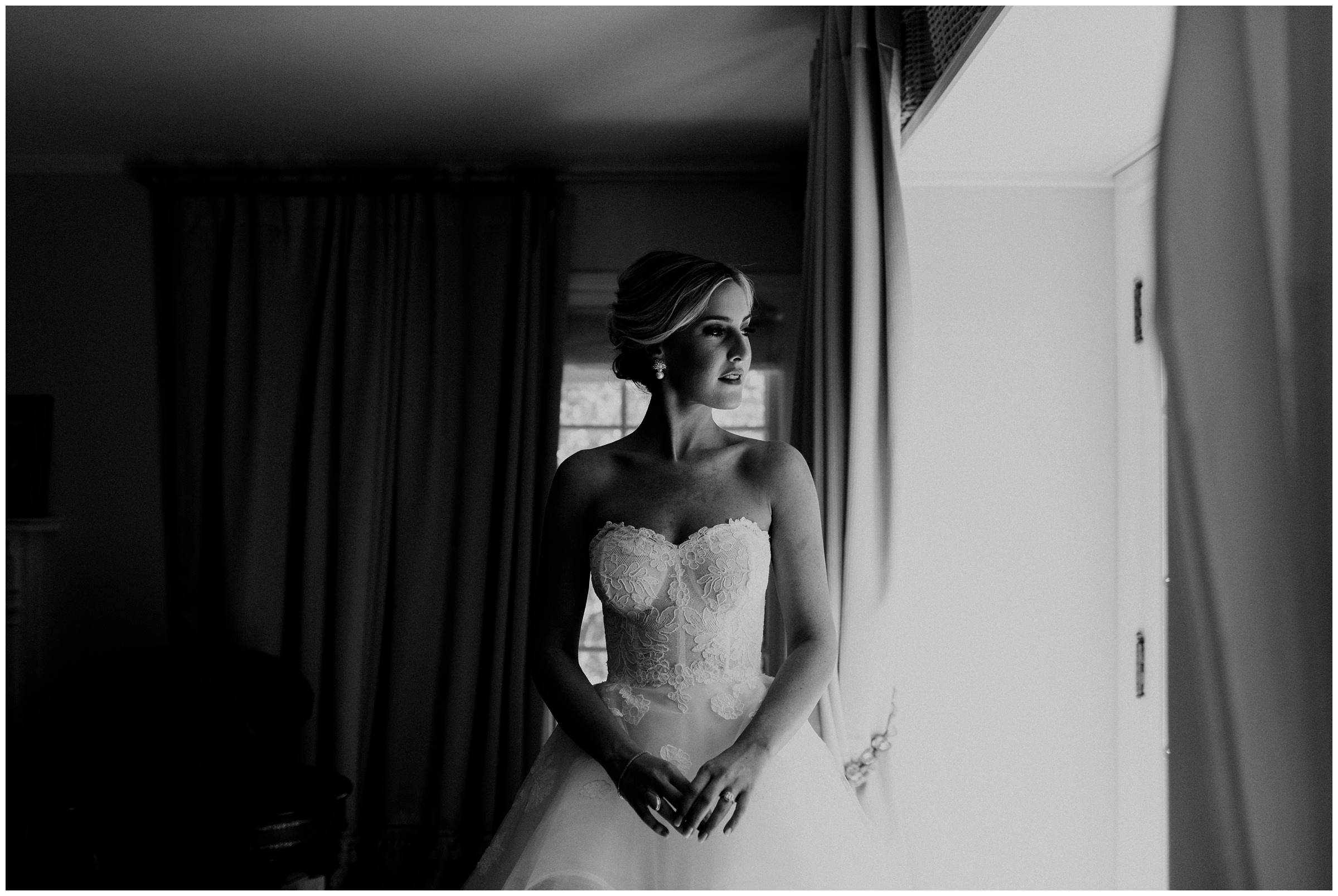 black and white photo of bride looking out the window at her home