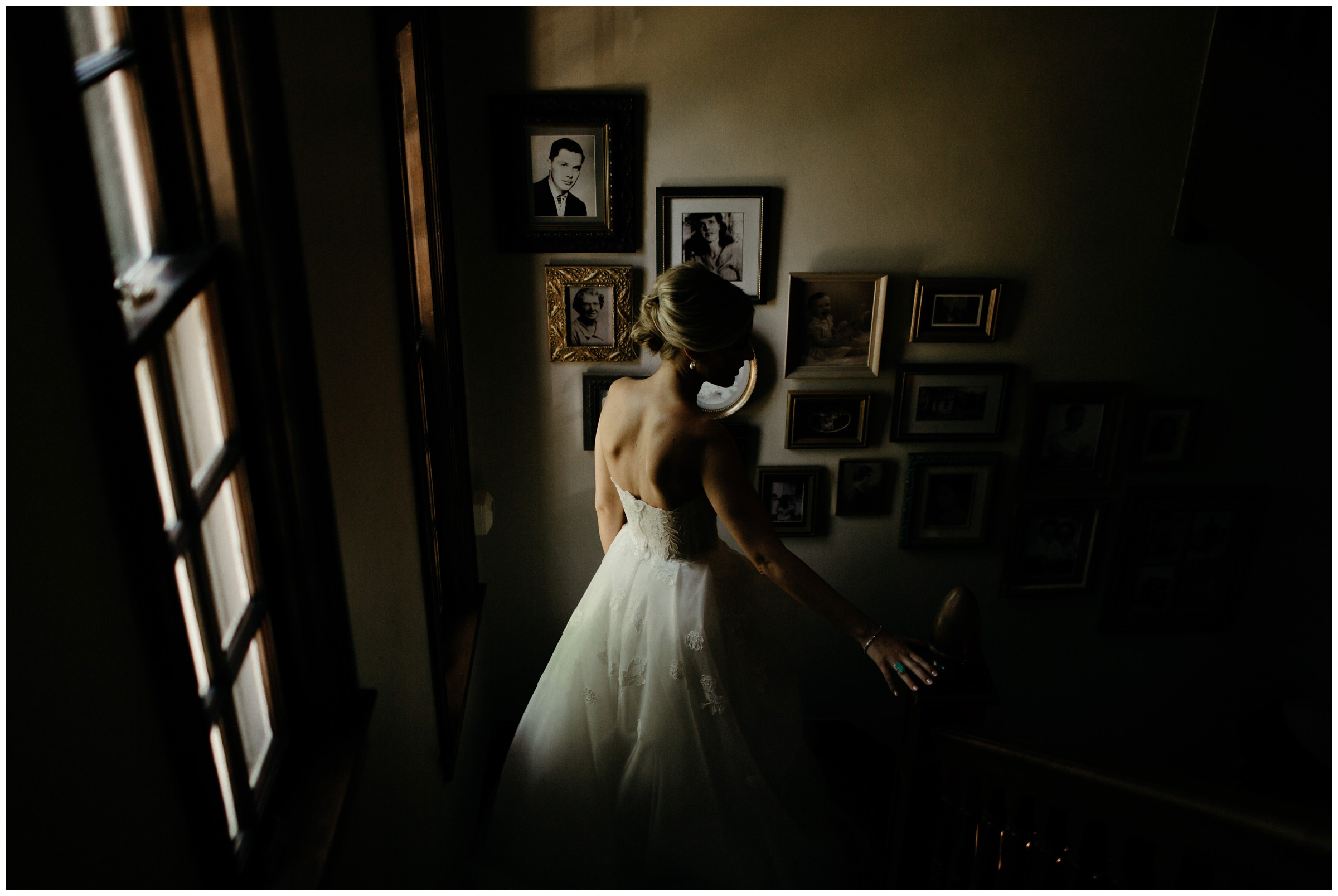 moody photo of bride walking down childhood home stairs