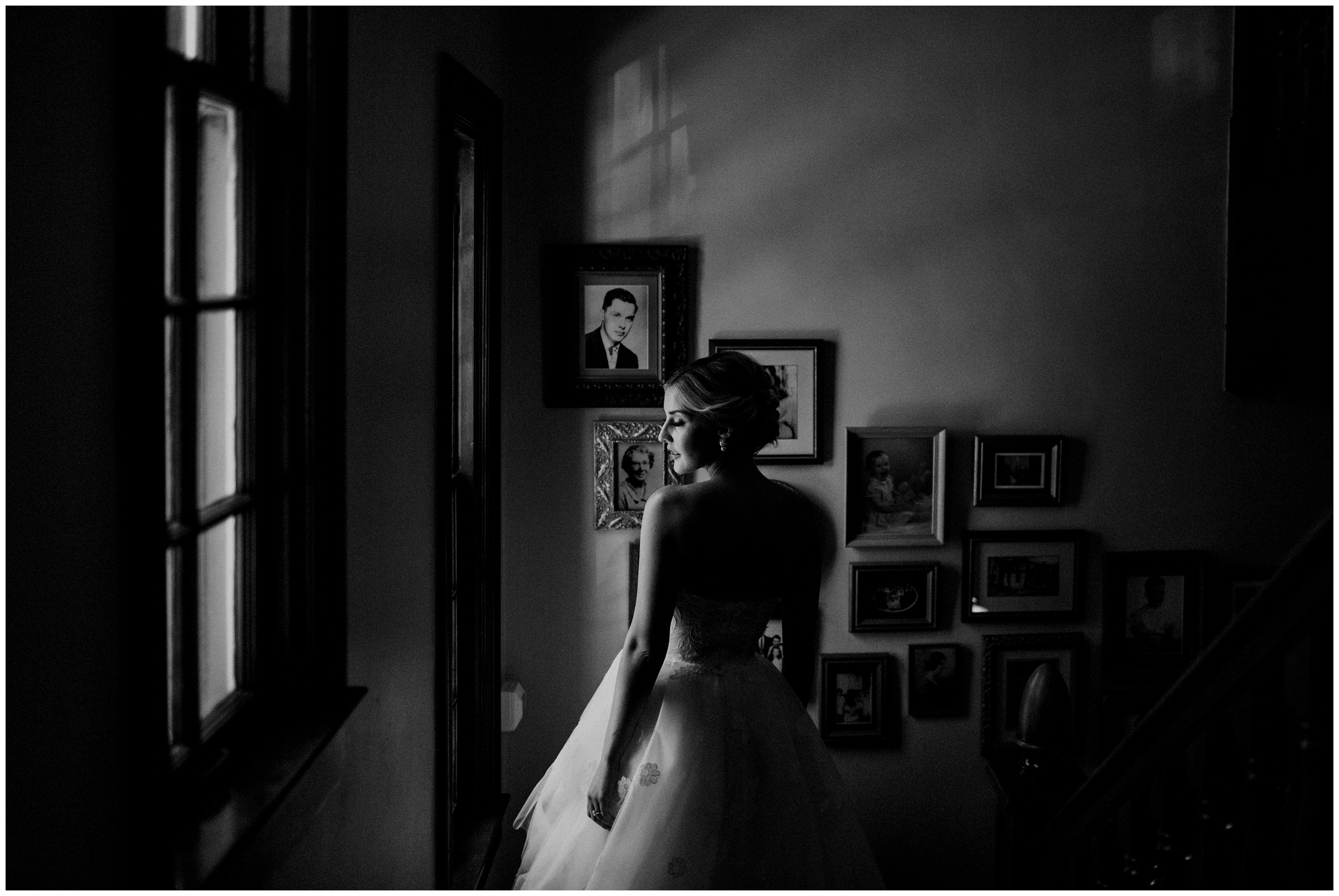 moody photo of bride looking out window