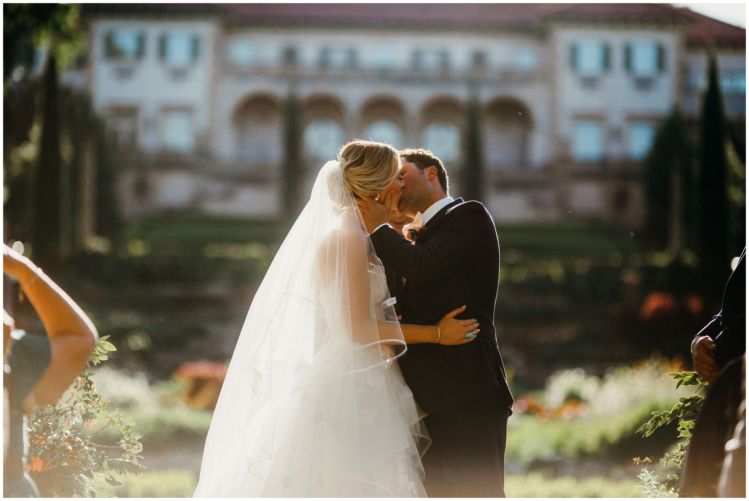 bride and grooms first kiss at philbrook museum wedding