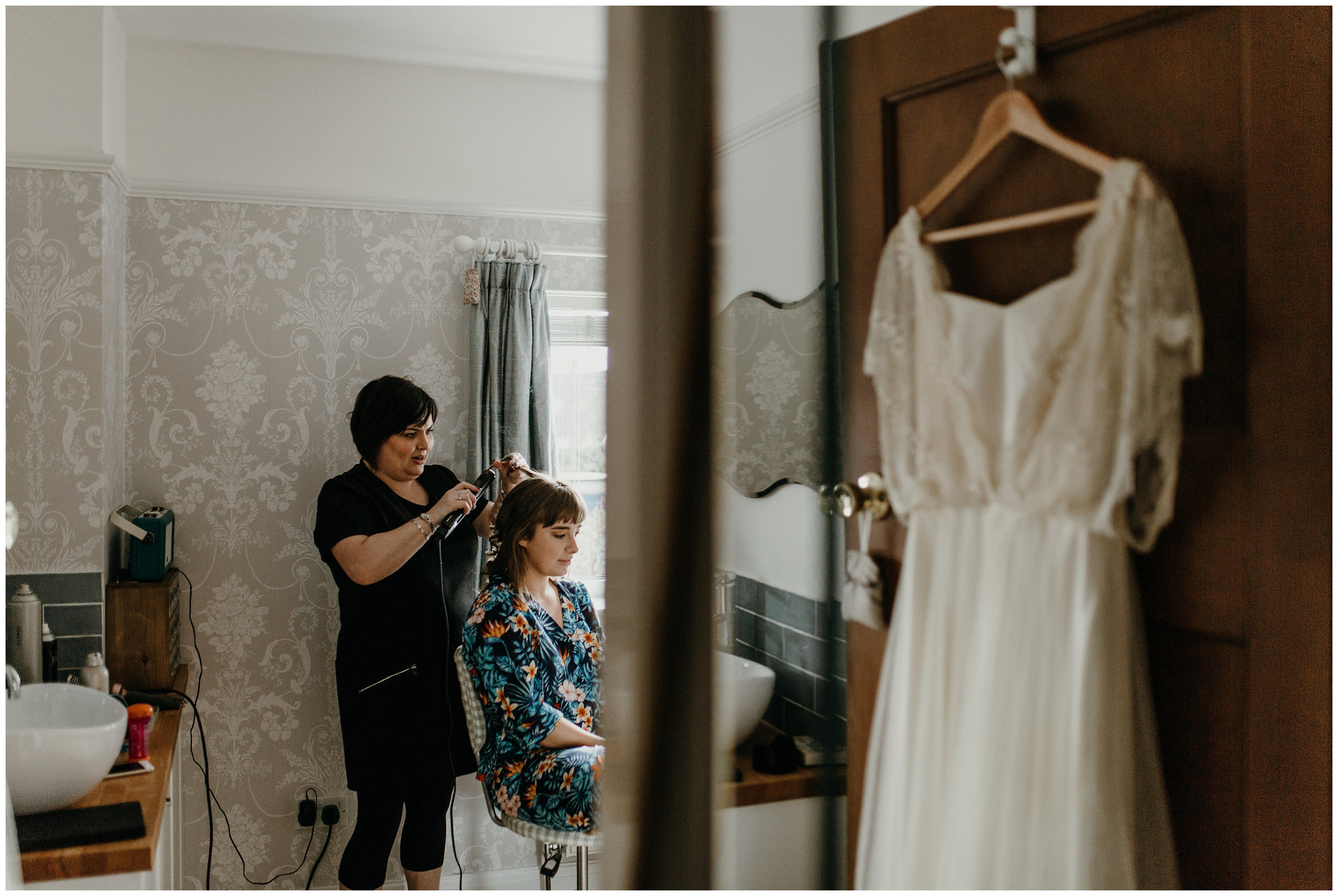 bride getting ready with wedding dress in view