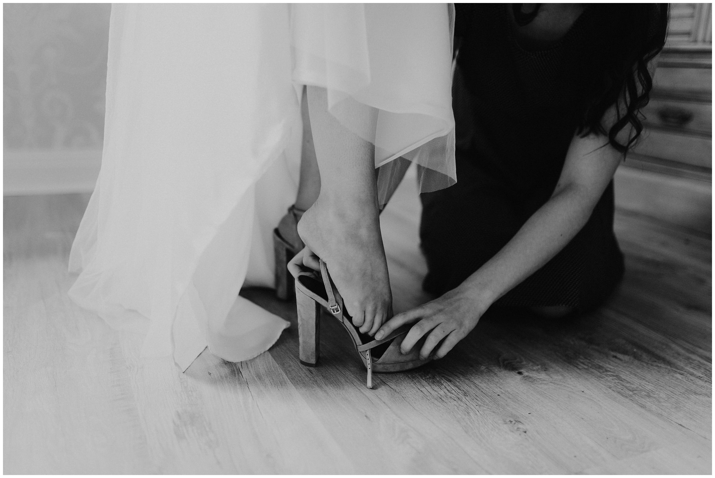 sister helps bride put on shoes