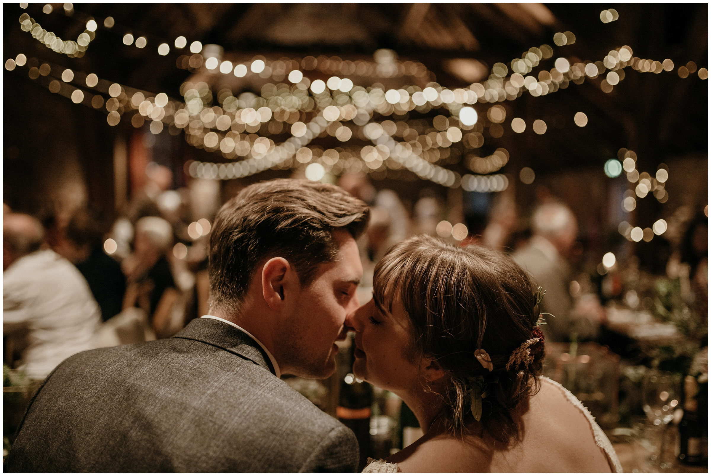 couple kissing at their wedding reception at the poppleton tithe barn