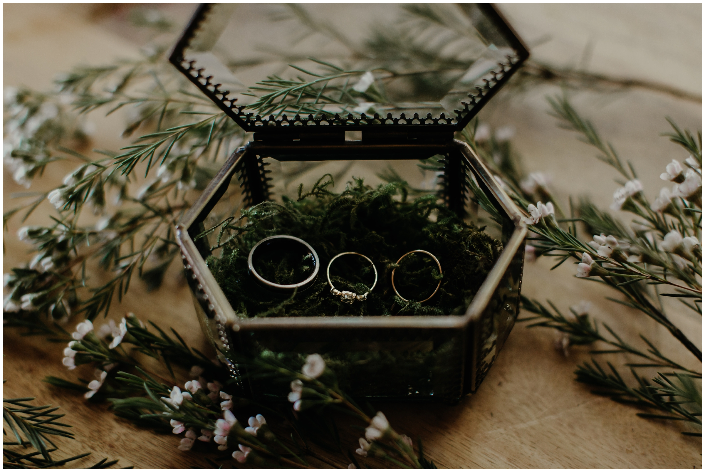 brass box with wedding rings and moss
