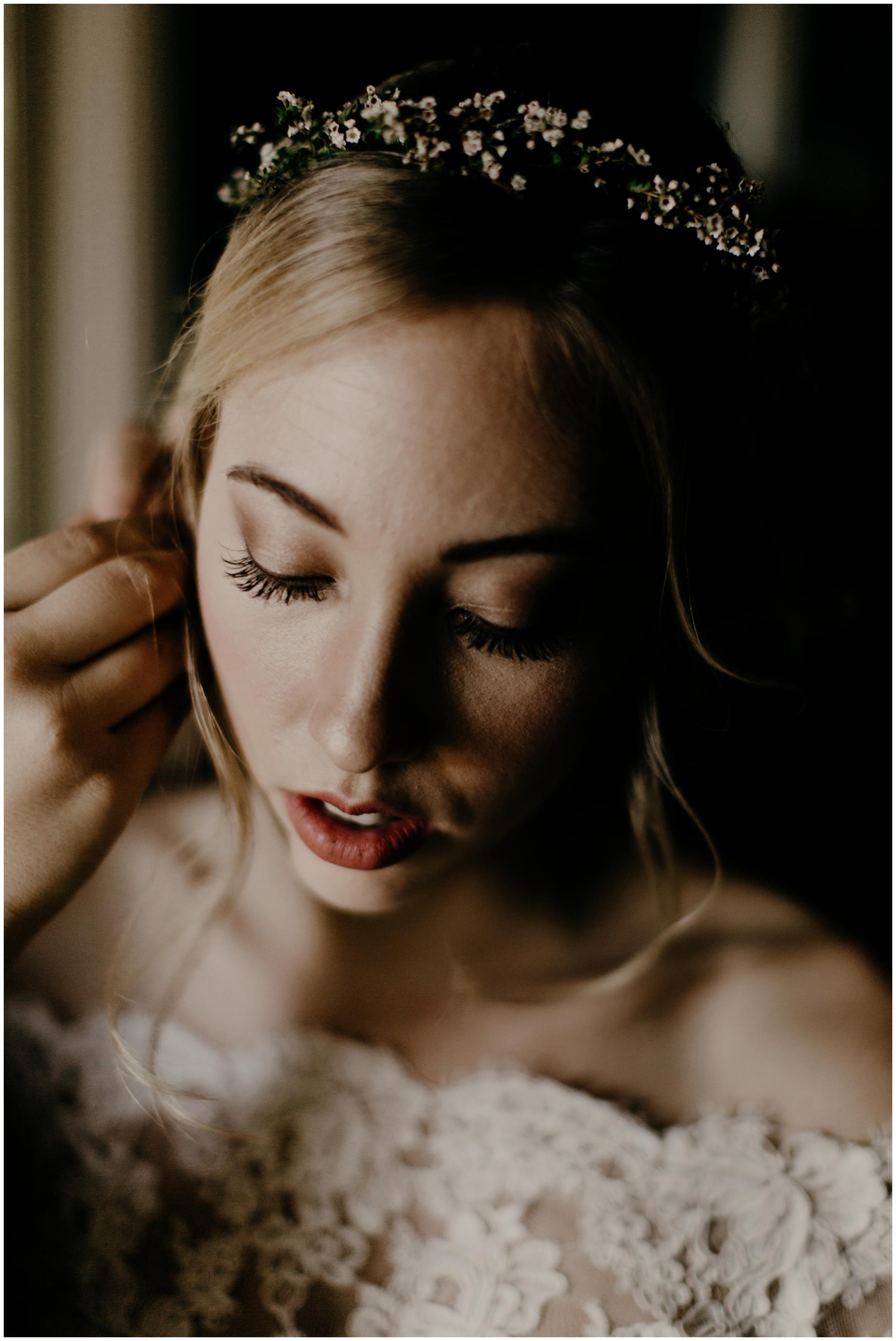 bride getting earrings in