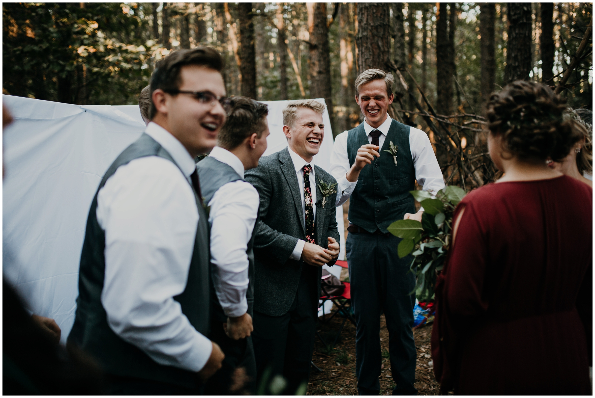 groom laughing with friends at wedding