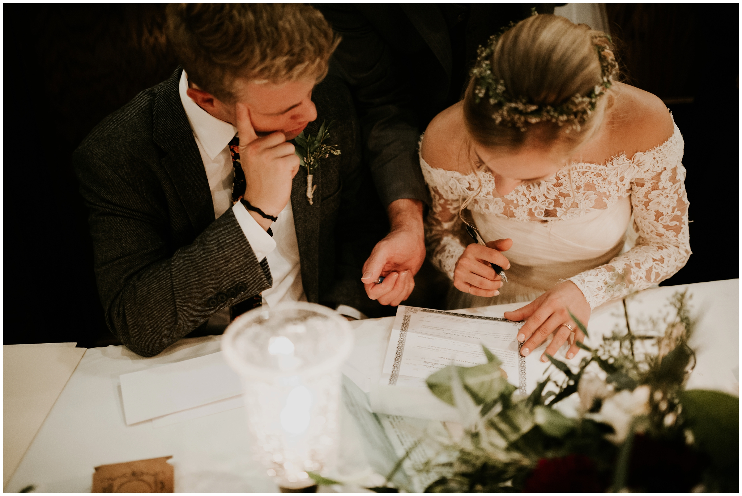 bride and groom signing marriage certificate