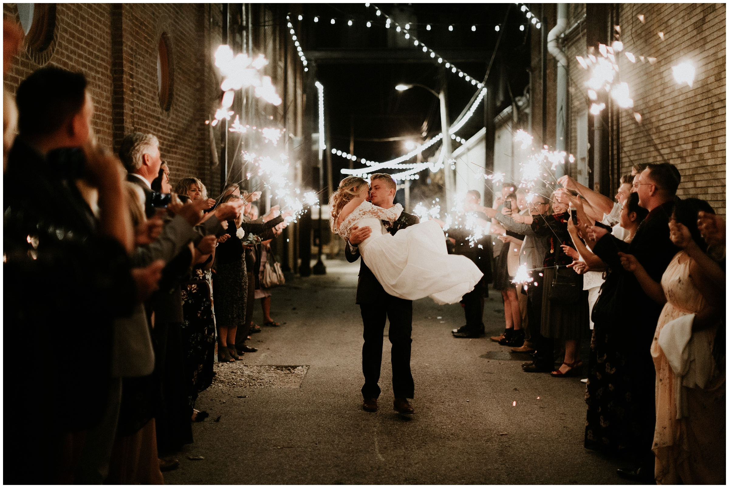 groom picks up bride during sparkler exit downtown rogers arkansas wedding