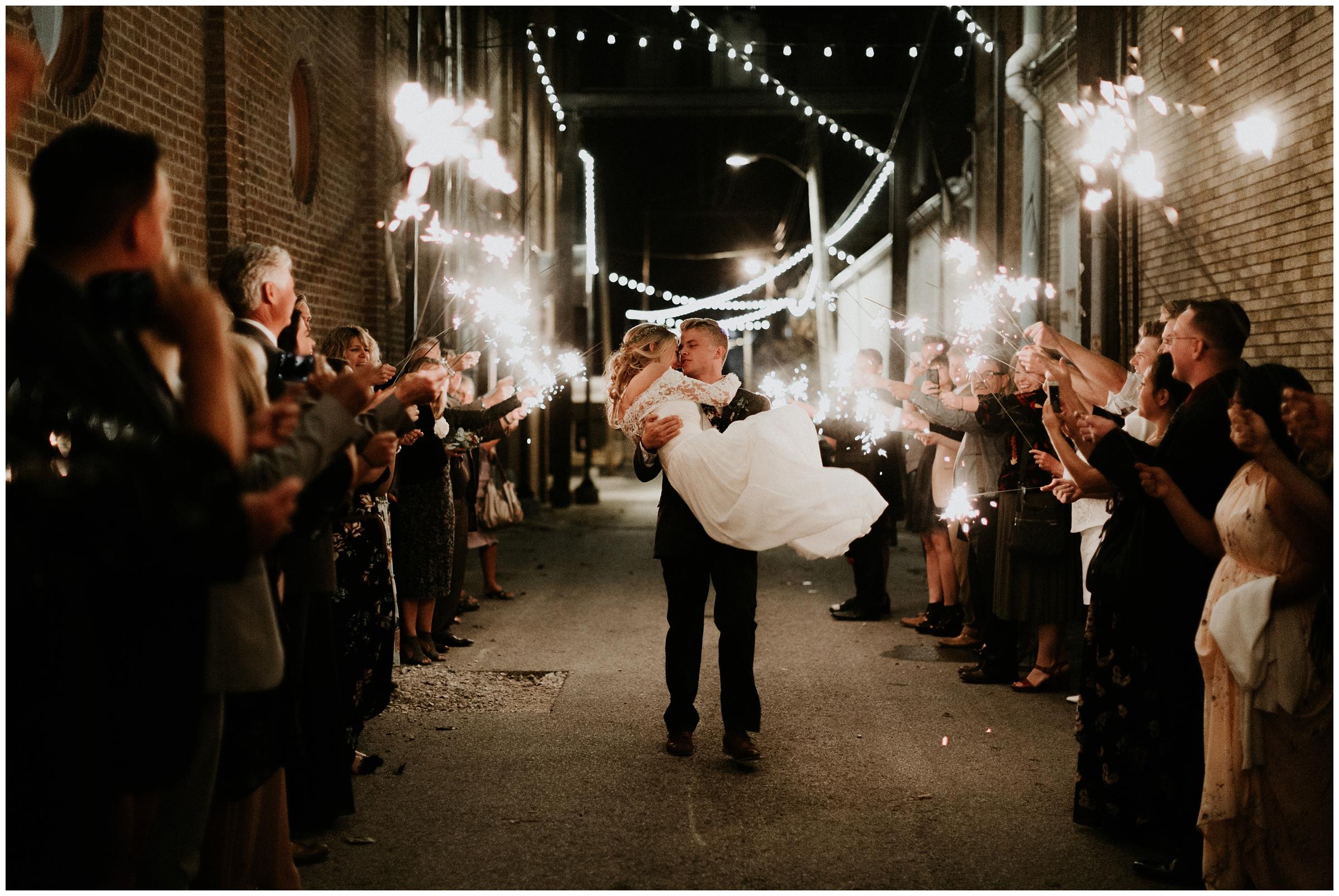 groom picks up bride during sparkler exit downtown rogers arkansas wedding