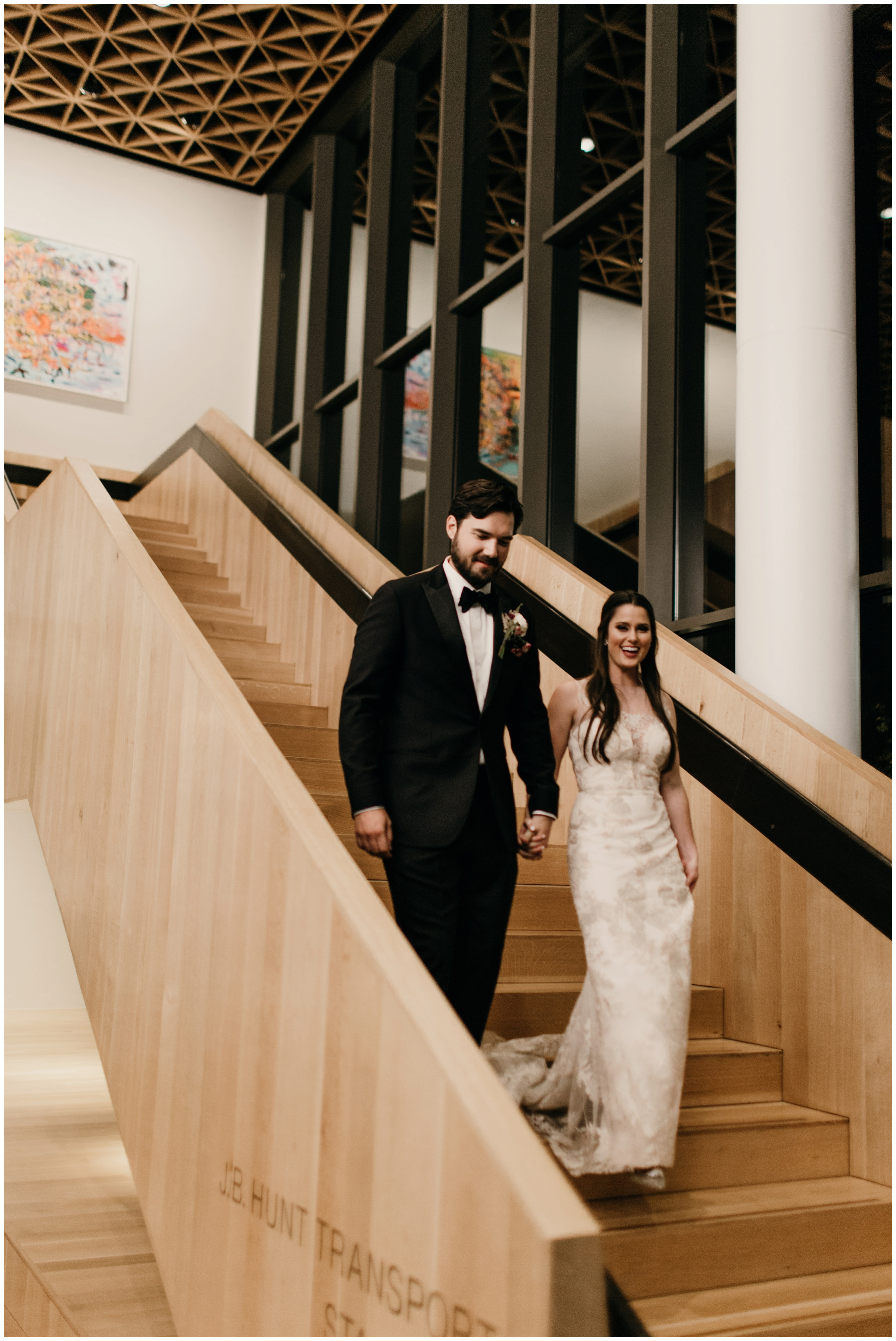 bride and groom walking down stairs at walton arts center