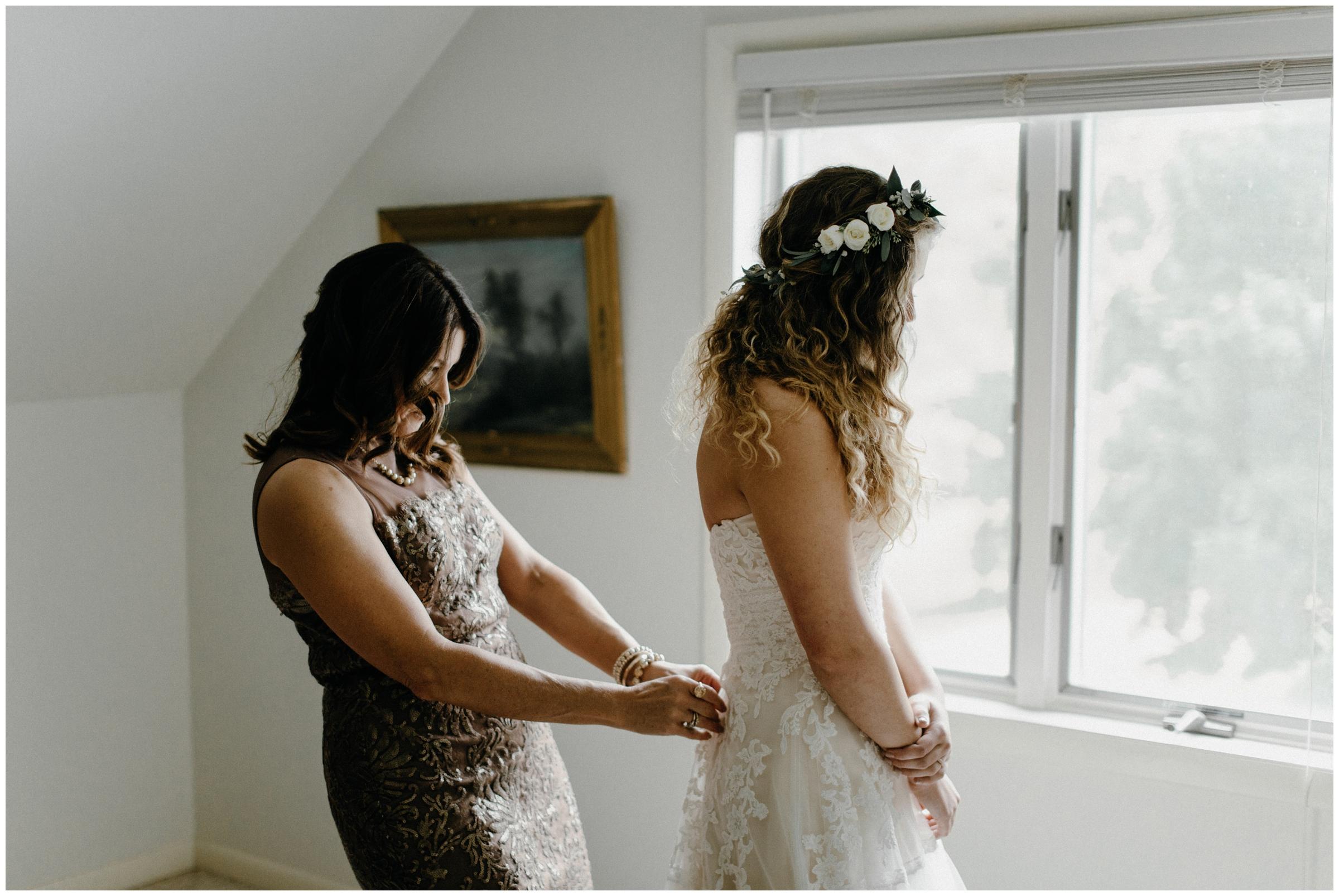 mother zips bride into her wedding dress in springfield missouri