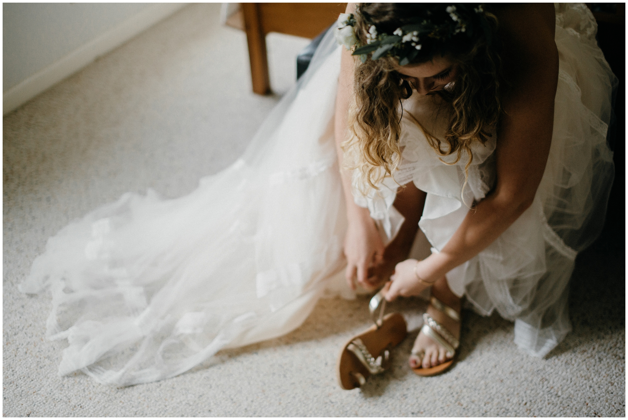 bride puts on sandals for outdoor wedding