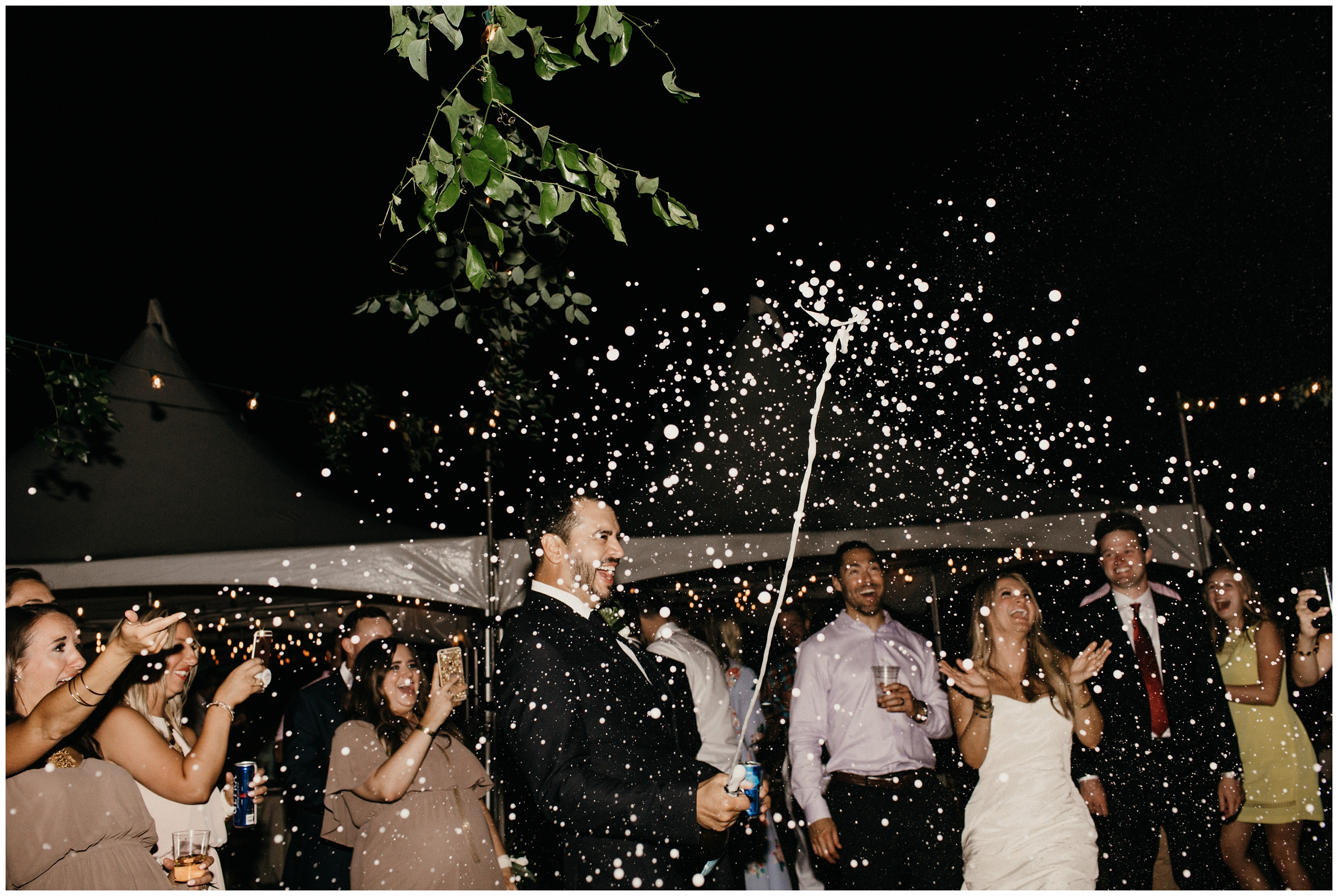 groom popping champagne at wedding reception