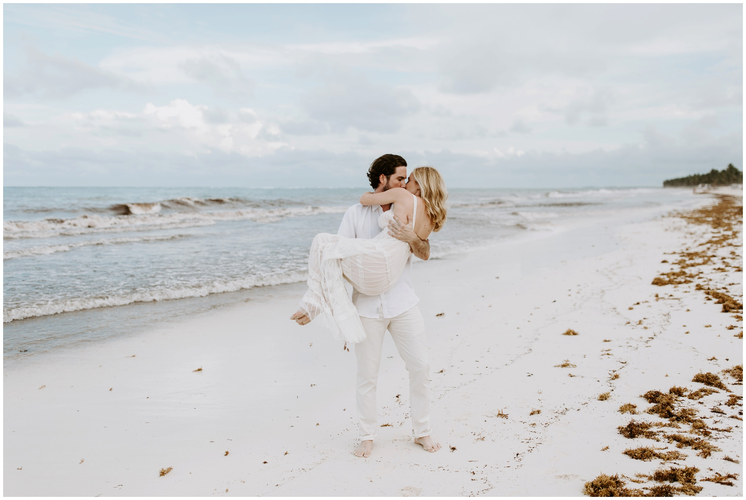 groom picks up bride on beach