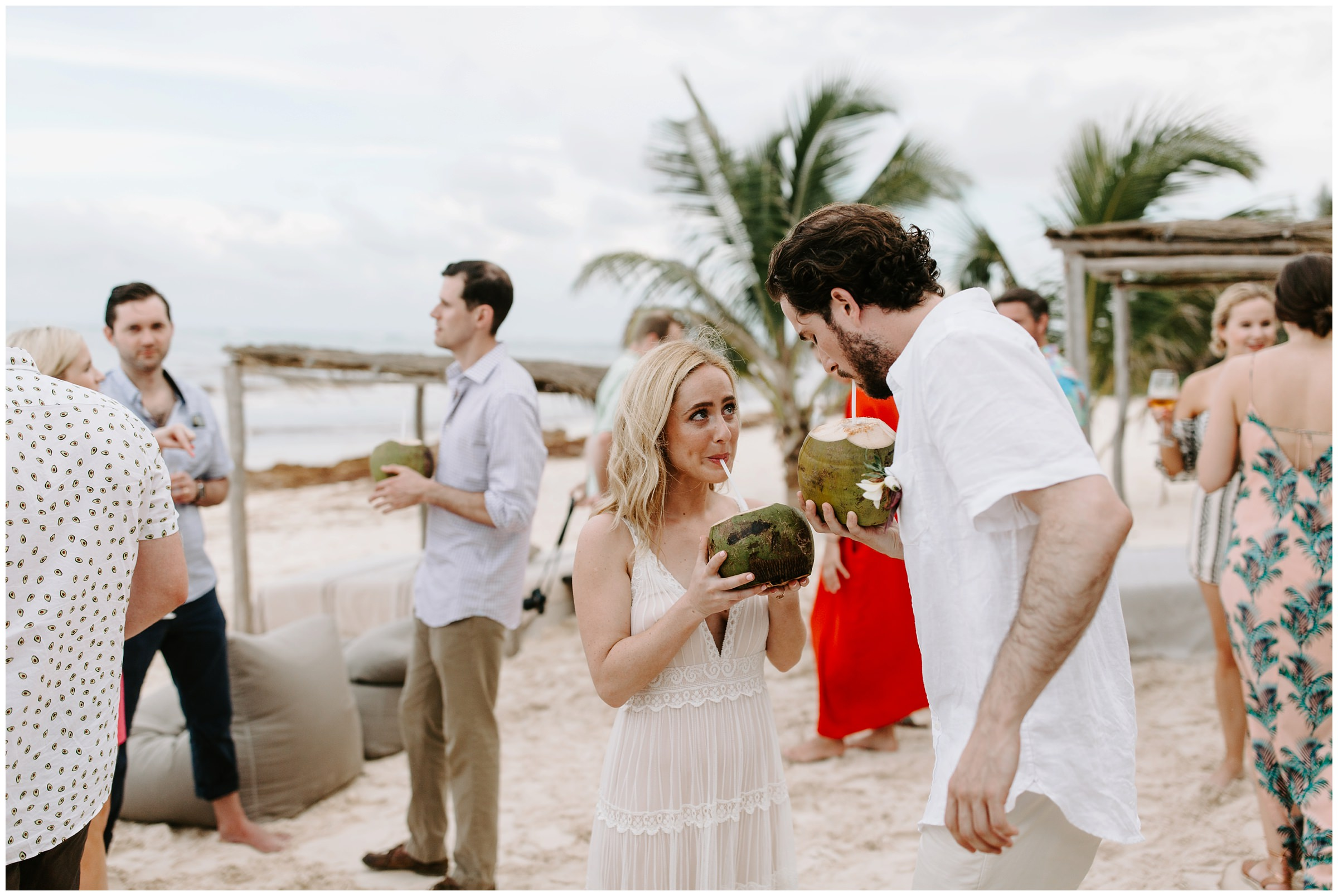 bride and groom drinking out of coconuts