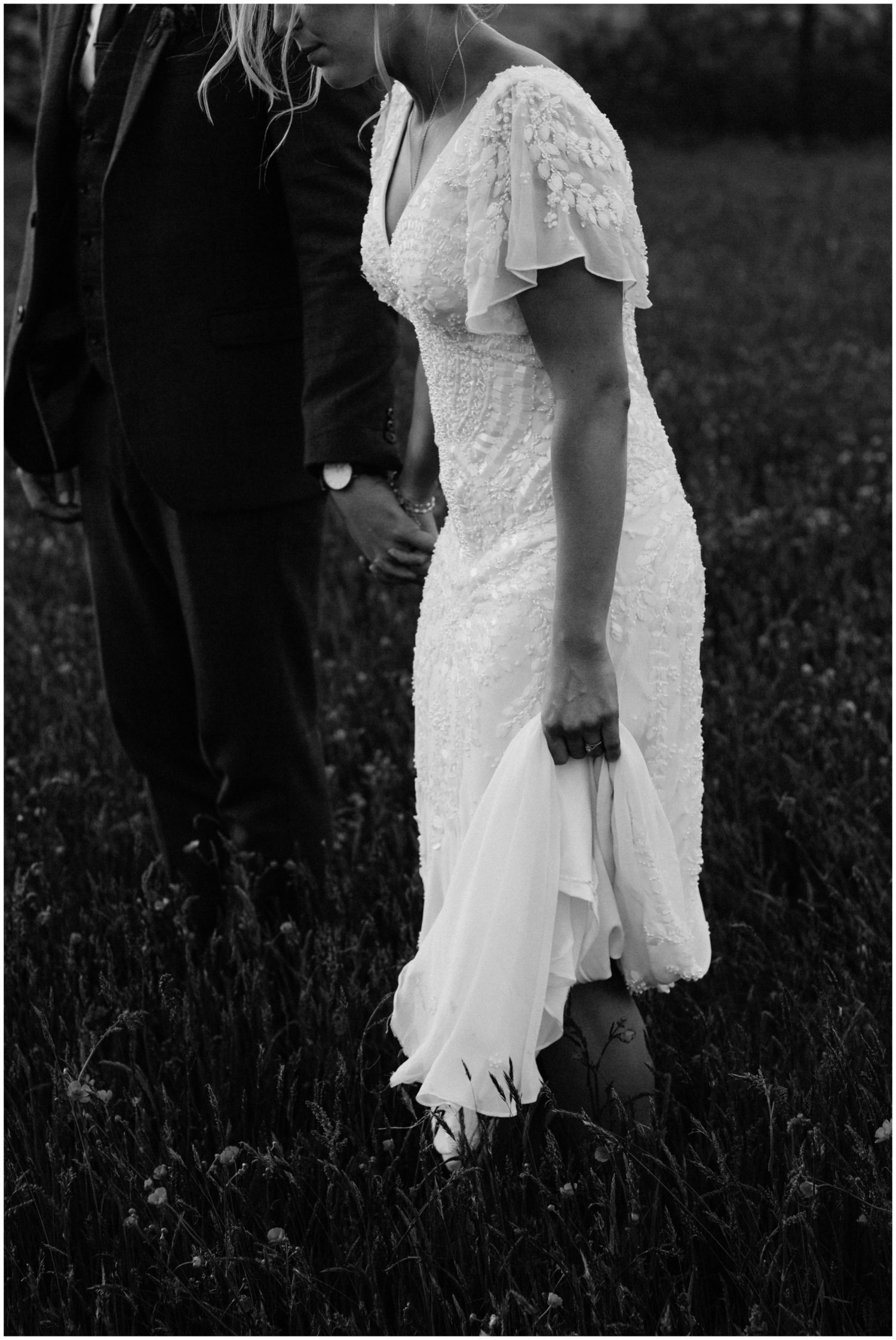 bride holds dress while walking