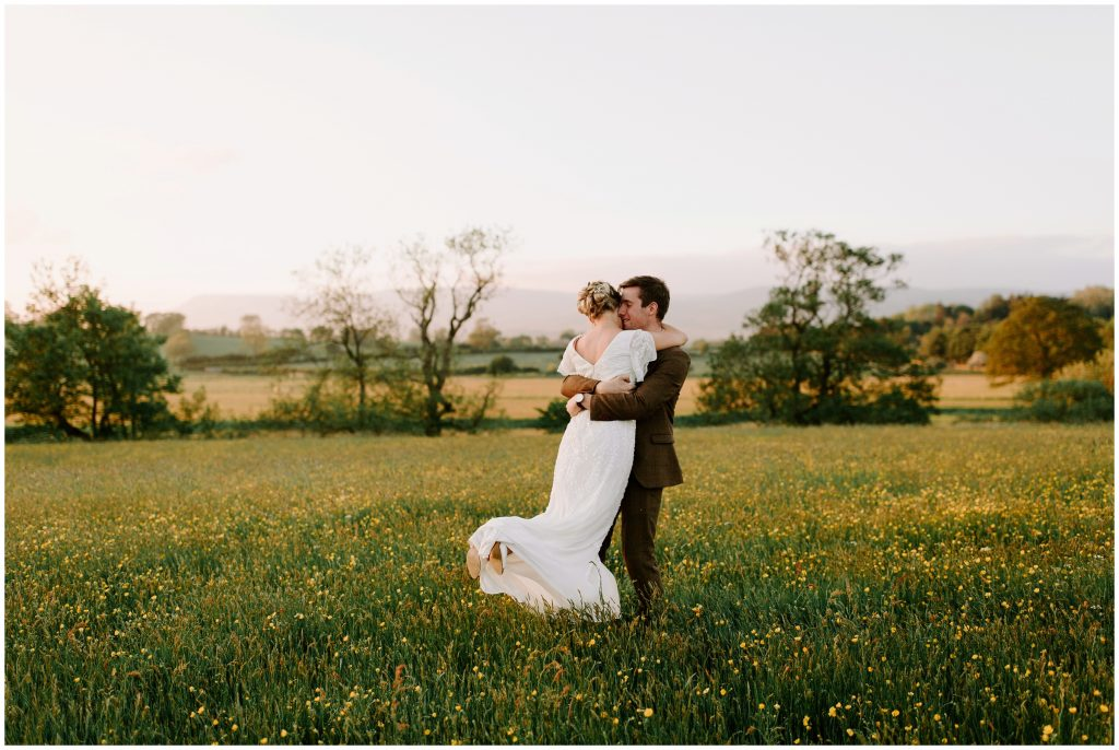 groom spinning bride around at sunset on wedding day