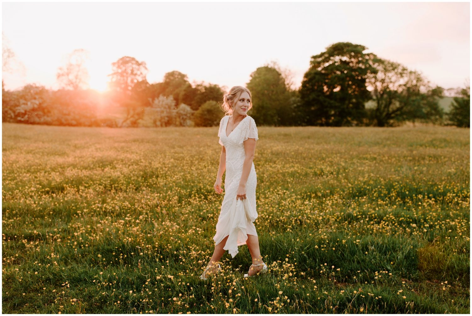 bride walking in field of flowers