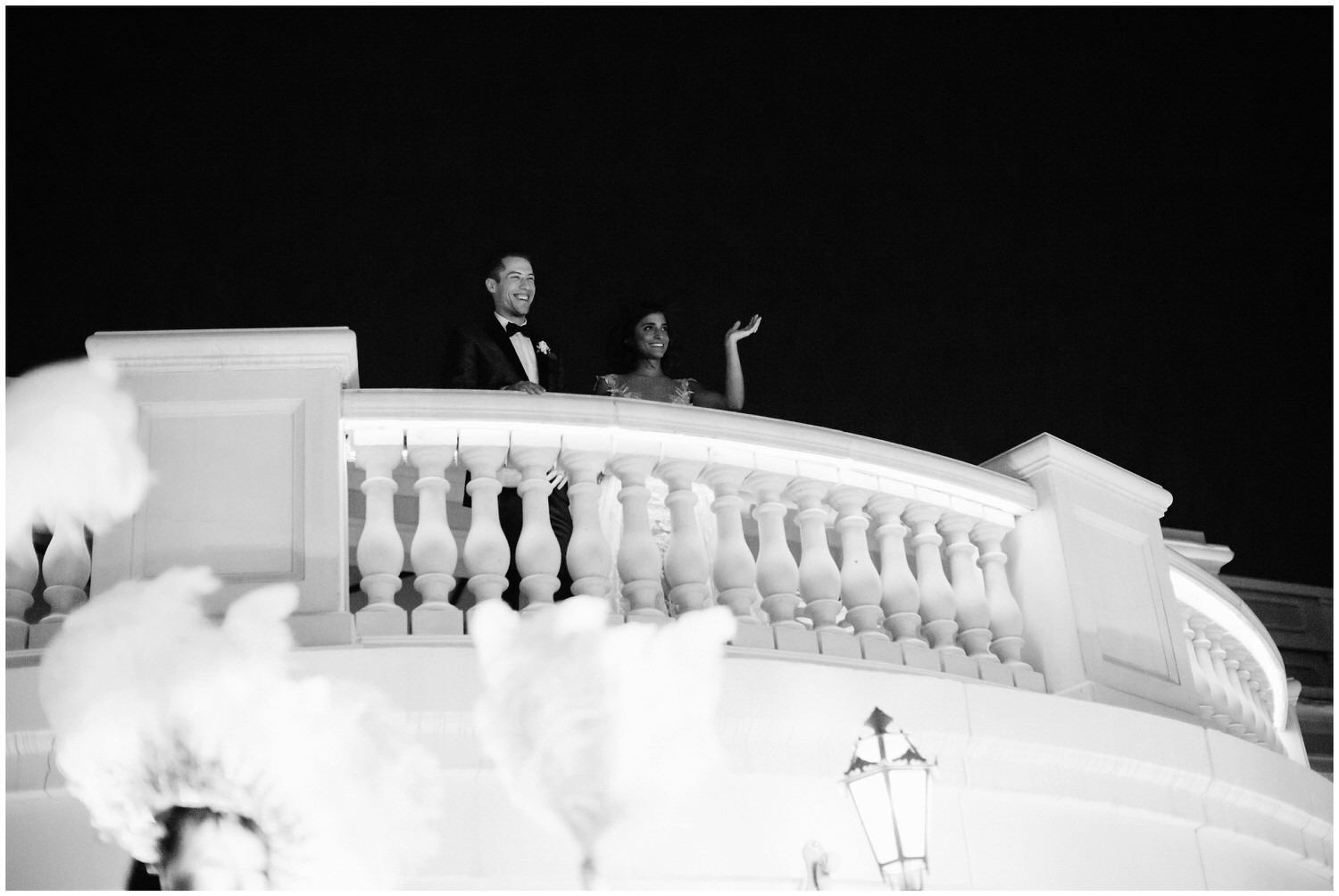 couple waving hello over balcony