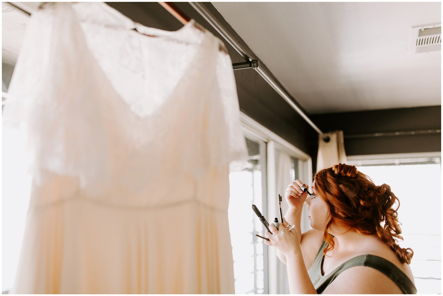 bride getting ready next to wedding dress