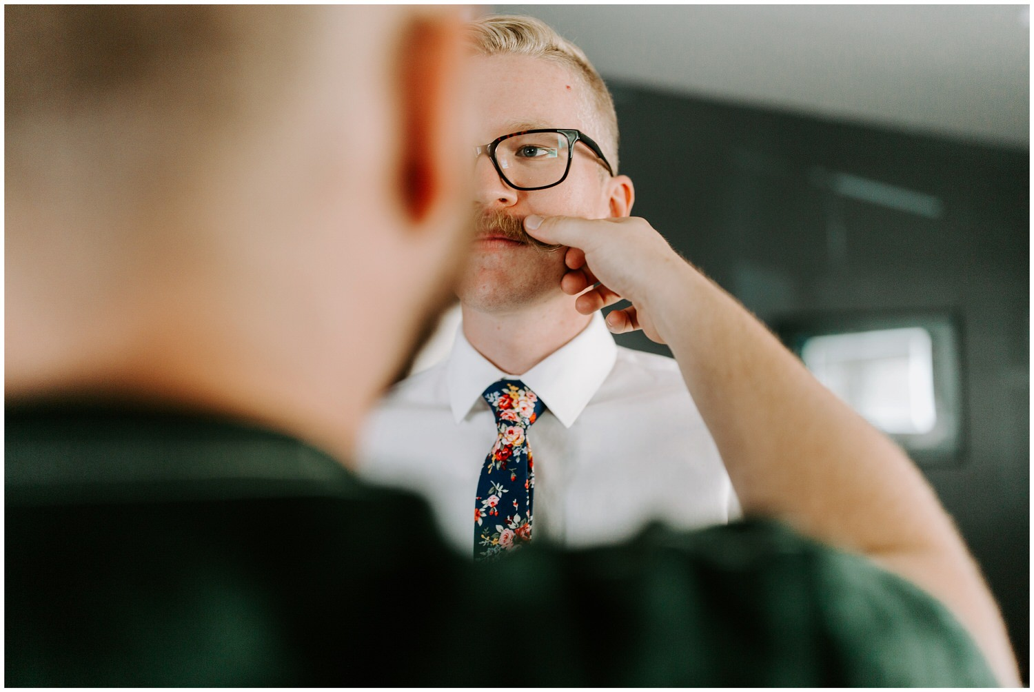 groom getting ready with handle bar mustache
