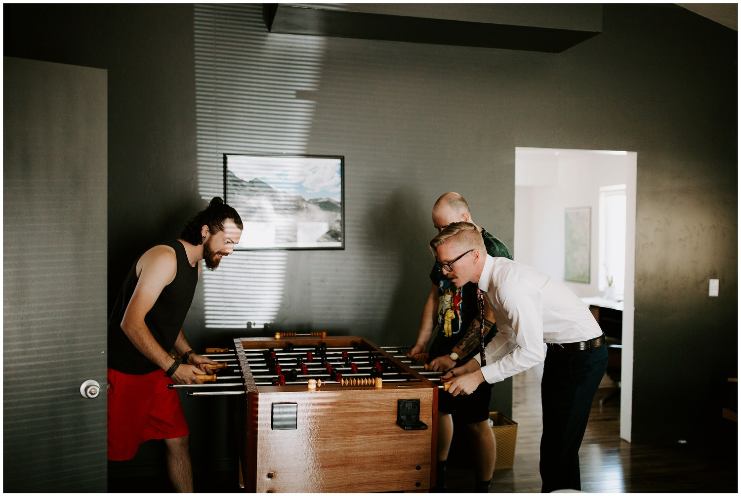groom and groomsmen playing foosball in airbnb